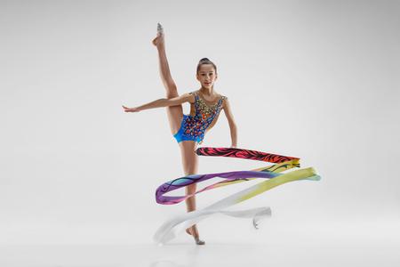 Le portrait de la belle jeune femme brune gymnaste exercice de callisthénie avec ruban bleu sur fond de studio blanc. Concept de gymnastique artistique. Modèle caucasien en pleine hauteur Banque d'images
