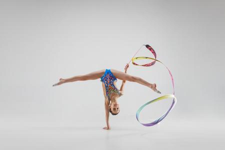 El retrato de la hermosa joven morena gimnasta entrenamiento calilistenia ejercicio con cinta azul sobre fondo blanco de estudio. Concepto de gimnasia artística. Modelo caucásico en altura completa Foto de archivo