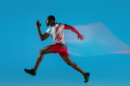 Full length portrait of active young african muscular running man, isolated over blue studio background with flashes of light