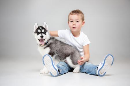 Portrait of a joyful little boy having fun with siberian husky puppy on the floor at studio. The animal, friendship, love, pet, childhood, happiness, dog, lifestyle concept