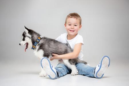 Portrait of a joyful little boy having fun with siberian husky puppy on the floor at studio. The animal, friendship, love, pet, childhood, happiness, dog, lifestyle concept Reklamní fotografie - 113094302