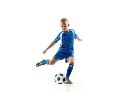Niño con balón de fútbol haciendo patada voladora, aislado en blanco. futbolistas de fútbol en movimiento sobre fondo de estudio. Montar niño saltando en acción, salto, movimiento en el juego. Foto de archivo