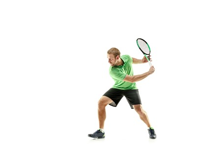 The one caucasian man playing tennis isolated on white background. Studio shot of fit young player at studio in motion or movement during sport game.. Banque d'images