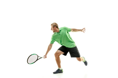 The one caucasian man playing tennis isolated on white background. Studio shot of fit young player at studio in motion or movement during sport game.. 写真素材 - 113095030