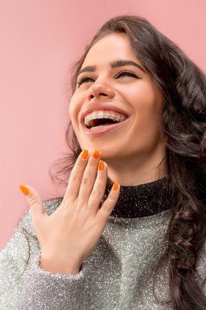 Schöne junge Frau mit Zahnspangen auf Rosa