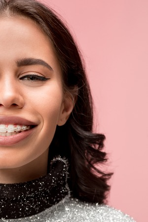 Beautiful young woman with teeth braces on pink. half face of pretty girl 写真素材