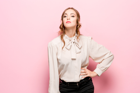 The serious frustrated young beautiful business woman with pencil on pink studio background Stock Photo