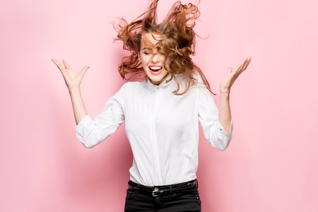 The young womans portrait with happy emotions on pink background