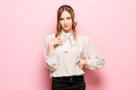A woman asks who I am, showing on themselves fingers. Beautiful female half-length portrait isolated on pink studio backgroud. Young emotional surprised woman looking at camera.Human emotions, facial expression concept
