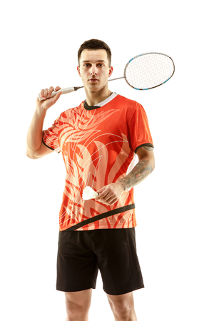 Young man badminton player standing over white studio background. Fit male athlete Фото со стока