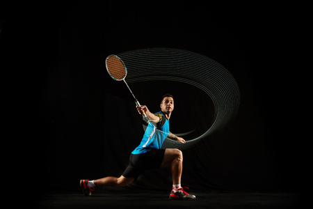 Young man playing badminton over black studio background. Fit male athlete isolated on dark with led light trail . badminton player in action, motion, movement. attack and defense concept