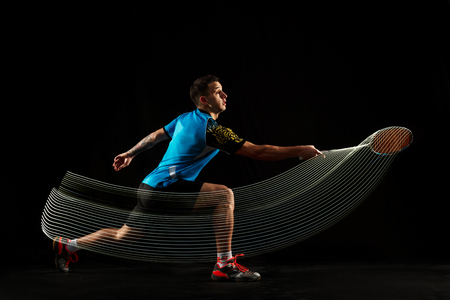 Young man playing badminton over black studio background. Fit male athlete isolated on dark with led light trail . badminton player in action, motion, movement. attack and defense concept 版權商用圖片 - 113260815
