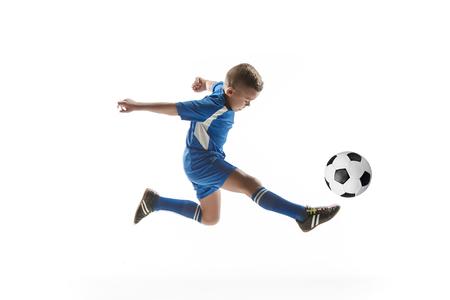 Jonge jongen met voetbal die vliegende schop doet, die op wit wordt geïsoleerd. voetbal voetballers in beweging op studio achtergrond. Fit springende jongen in actie, springen, beweging in het spel. Stockfoto
