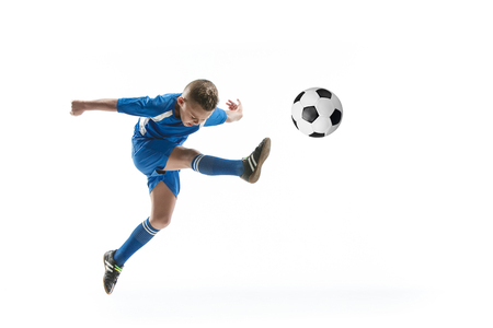 Young boy with soccer ball doing flying kick, isolated on white. football soccer players in motion on studio background. Fit jumping boy in action, jump, movement at game. Stock Photo