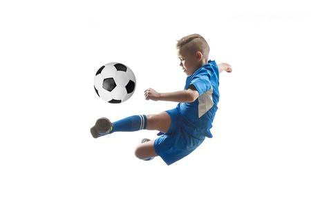 Niño con balón de fútbol haciendo patada voladora, aislado en blanco. futbolistas de fútbol en movimiento sobre fondo de estudio. Montar niño saltando en acción, salto, movimiento en el juego.