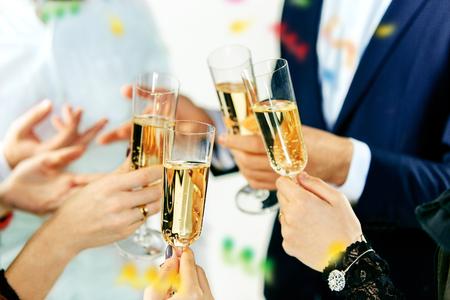 Feier. Hände, die die Gläser Champagner und Wein halten, die einen Toast machen.