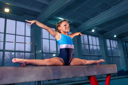 The beautiful little girl is engaged in sports gymnastics on a log at gym. Foto de archivo - 113874465