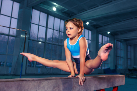 The beautiful little girl is engaged in sports gymnastics on a log at gym.