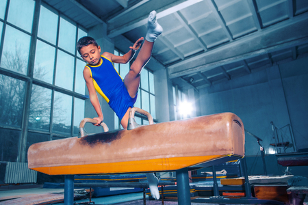 The sportsman performing difficult gymnastic exercise at gym. 스톡 콘텐츠