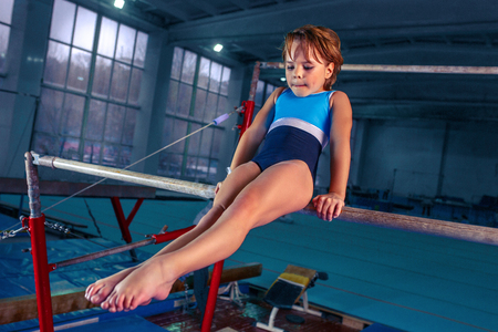 The beautiful little girl is engaged in sports gymnastics on a parallel bars at gym. 免版税图像