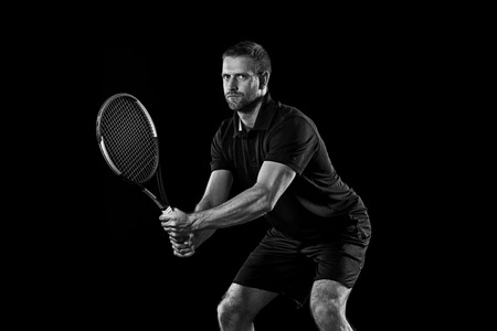 The one caucasian man playing tennis isolated on black