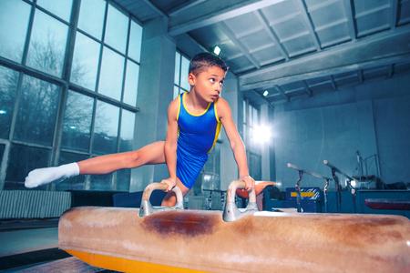 El deportista realizando difícil ejercicio gimnástico en el gimnasio.