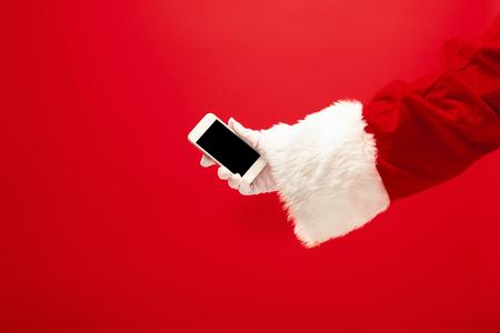 Père Noël tenant un téléphone portable prêt pour la période de Noël sur un studio rouge Banque d'images