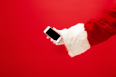 Santa Claus holding mobile phone ready for Christmas time on red studio Фото со стока