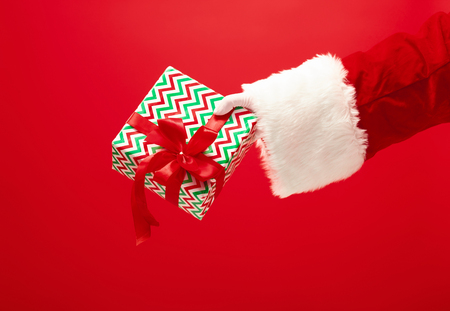 The hand of santa claus holding a gift on red 스톡 콘텐츠