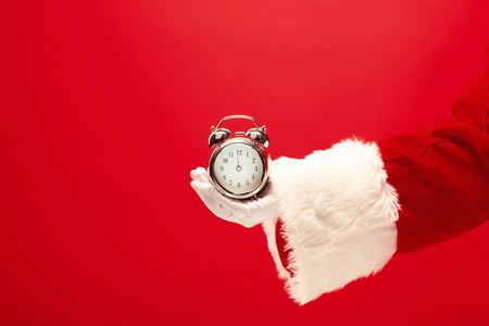 Santa holding an old alarm clock on red