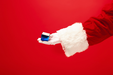 The hand of santa claus holding a gift on red 스톡 콘텐츠 - 113874222