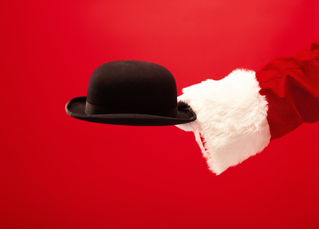 The hand of santa claus holding a black hat on red