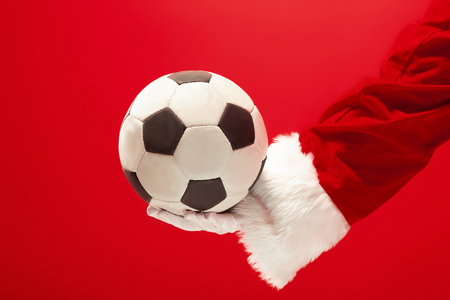 Santa Claus holding a football ball isolated on red studio