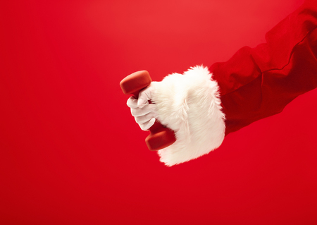 Holidays and celebrations, New year, Christmas, sports, bodybuilding, healthy lifestyle - Santa Claus with dumbbells. 免版税图像