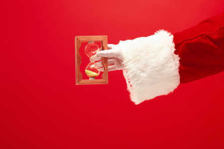 Santa holding an old sand clock on red