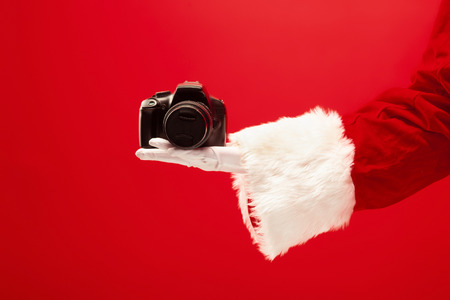 The hand of santa claus holding a camera on red