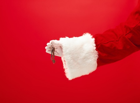 The hand of santa claus holding a apartment or car keys as gift on red