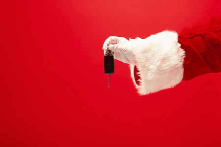 The hand of santa claus holding a gift on red Stock Photo