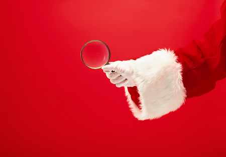 The hand of santa claus holding a magnifier on red