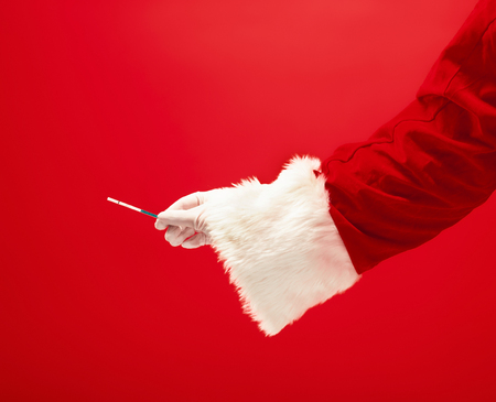 The hand of santa claus holding a pregnancy test on red 스톡 콘텐츠 - 113874187