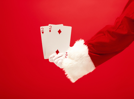 The hand of santa claus holding a playing cards on red 스톡 콘텐츠 - 113874072