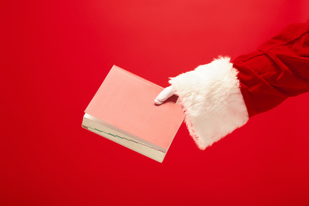 The hand of santa claus holding a notebook on red