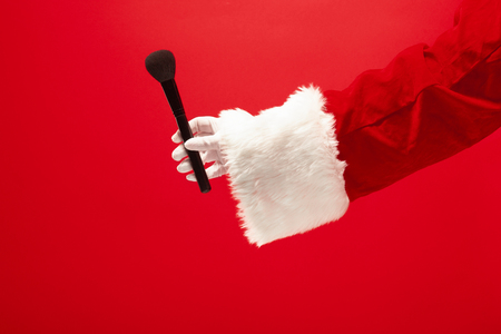 The hand of santa claus holding a makeup brush for powder on red