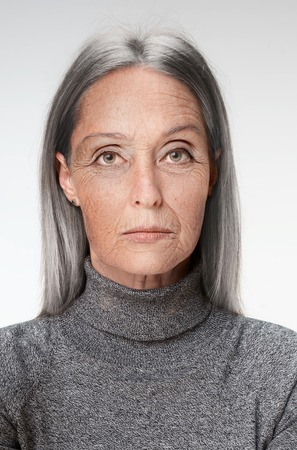 Portrait of sad senior woman on white. Studio shot