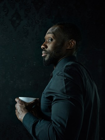 Stylish young african black man with white cup of coffee posing on dark studio background. Stock fotó