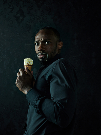 Portrait of sad afro american man holding ice cream over black studio background Imagens