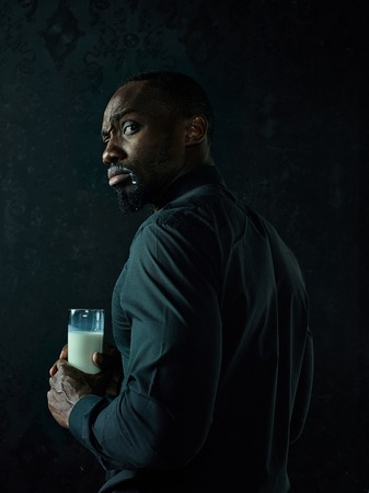 Healthy young african man holging cup of milk on a bllack studio background.