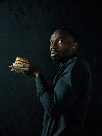 The young african american man eating hamburger and looking away on black studio background
