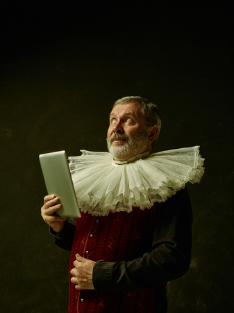 Official portrait of surprised historical governor from the golden age with corrugated round collar and laptop. Studio shot against dark wall.
