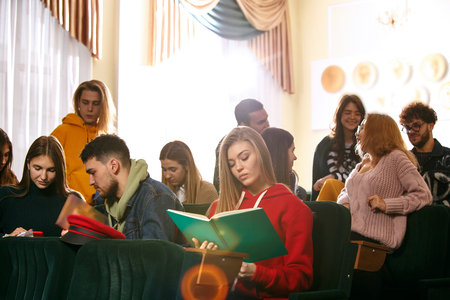 The group of cheerful students sitting in a lecture hall before lesson. Stok Fotoğraf